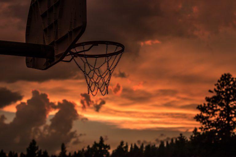 Un canestro da basketball al tramonto.