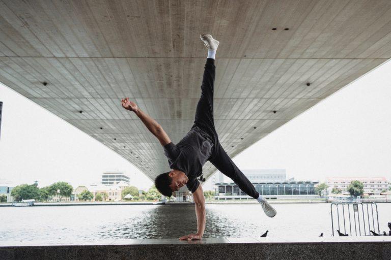 Un ragazzo esegue una verticale vicino a un fiume.